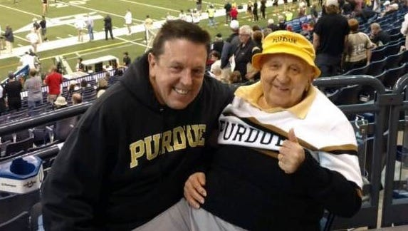 Mickey Kor, right, with his son, Alex, gives the thumbs up as he poses for a picture before Purdue's season football opener against Louisville at Lucas Oil Stadium in Indianapolis. Mickey Kor, a Purdue graduate, is a Holocaust survivor and long-time season ticket holder at Purdue.