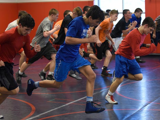 High school wrestlers find out there's much more to the sport than they might have envisioned. Here, Livonia Franklin's Nathan Atienza leads teammates during practice sprints.