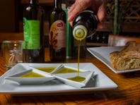 Antonio Durante, owner of Caffe Toscano, in Fort Myers, displays an assortment of olive oils available at his restaurant.