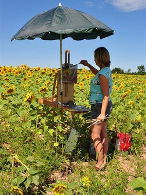 Pam Clausen paints a field of sunflowers in Kewaunee County.  She will be painting a flower still life at the Lakehaven Garden and Outdoor Living show on May 28.