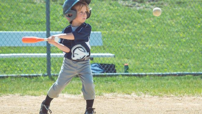 A little boy swings at an incoming baseball.