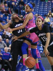 Delaware's Samone DeFreese (center) looks to a loose ball as she collides with James Madison's Kayla Cooper-Williams (left) and Lexie Butler of the Dukes pursues in the Blue Hens' 56-53 loss at the Bob Carpenter Center Friday.