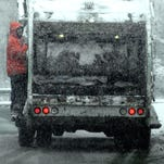 In this file photo, City of Poughkeepsie sanitation worker clings to the outside of his truck while traveling on South Cherry Street during the snowfall.