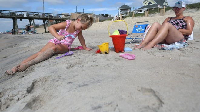 Ella Mae Prince digs a hole in the sand while her mother Trisha Prince relaxes on the beach in Surf City, N.C., Wednesday, June 24, 2020. The family was visiting the area from Nashville.