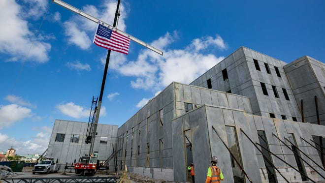 A 1,400 pound, 40 foot long steel beam that will be housed in the City Commission Chambers? ceiling is moved into place during a topping out ceremony for the new City Hall & Library in Boynton Beach on October 2, 2019.