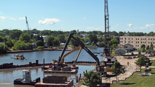 The Sheboygan River dredging operation, shown in this July 2011 photo, has reduced contaminant levels, but they still remain too high, according to a new federal report.