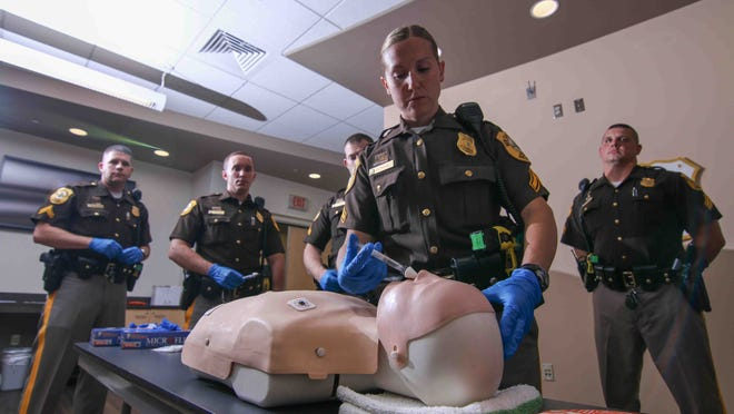 New Castle County Police Officer First Class L. Taylor administers water, which simulates the drug Narcan, into a practice mannequin on Thursday at the New Castle County Police public safety building. Narcan, a nasal spray, is used to reverse the effects of opiates during an overdose.