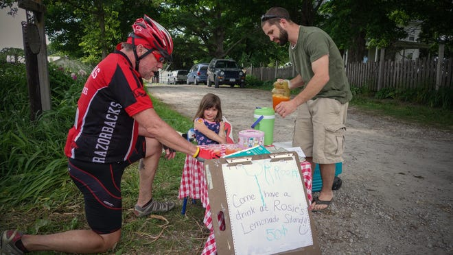 Dixon Novy of Davenport buys a strawberry lemonade from Dustin Krapfl and his daughter Rose, 4, outside there home near Coralville during the RAGBRAI pre-ride Friday, June 5, 2015.