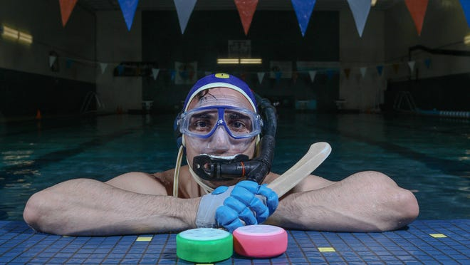 Andrei Savu pose for a photo after a underwater hockey game Saturday, May 16, 2015, at Clarence Fraim Senior Center in Wilmington, Delaware.