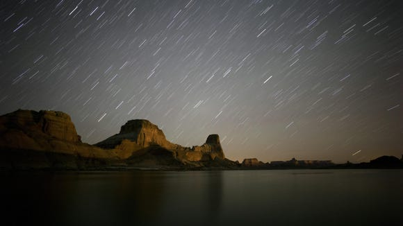 Jud appear to streak through the night sky above Gunsight Butte in Glen Canyon National Recreation Area in a long exposure image taken at Lake Powell. Stars appear to streak through the night sky above Gunsight Butte in Glen Canyon National Recreation Area in a long exposure image taken at Lake Powell.