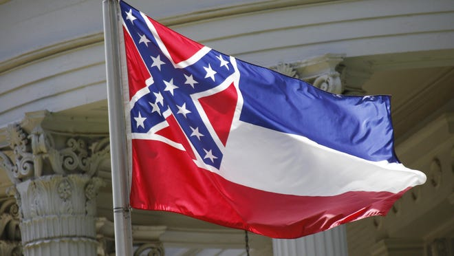 The state flag of Mississippi is unfurled against the front of the Governor's Mansion.