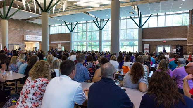 Teachers and staff gather in Lakeview High School's cafeteria during their opening meeting.