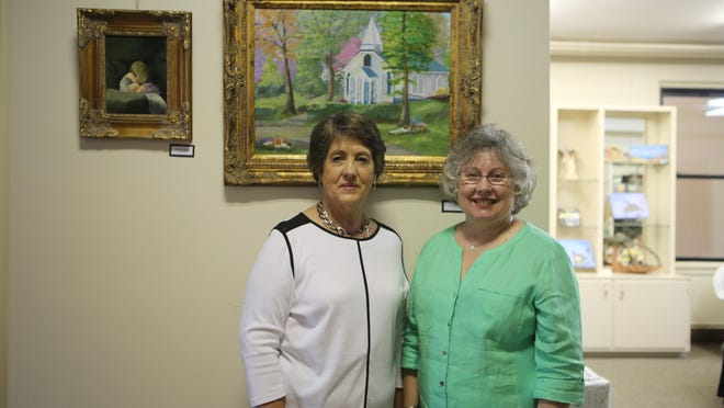 Tommie Campbell, left, and her aunt, Jan Sessions, decided to learn how to paint after they retired. They have completed close to 200 paintings in the past five years. Two of their favorites are shown behind them: Campbell's 'Brotherly Love' and Sessions' 'Historic Church in Helen, Ga.' Their work is on display through June 29 in the upstairs gallery of The Ned in downtown Jackson.