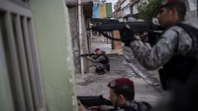 Brazil's national security force officers aim their weapons during a police operation in search for criminals in Vila do Joao, part of the Mare complex of slums, during the Summer Olympics in Rio de Janeiro, Brazil, Thursday, Aug. 11, 2016. A police officer has died after being shot in the head when he and two others working security at the Rio Olympics got lost near a slum and encountered gunfire. (AP Photo/Felipe Dana)