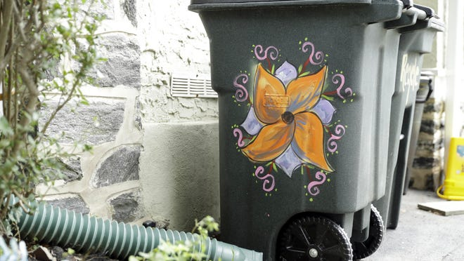 This Thursday, Aug. 25, 2016, photo shows Esther Cohen-Eskin's garbage can that was defaced with a large swastika and then she repainted as a flower in Havertown, Pa. The neighborhood has rallied around the Jewish family and also painted their trashcans to show their support. Photo/Matt Rourke