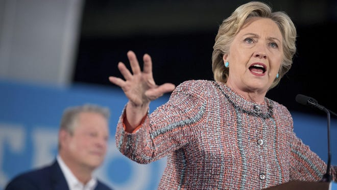 Democratic presidential candidate Hillary Clinton, accompanied by former Vice President Al Gore, left, speaks at a rally at Miami Dade College in Miami, Tuesday, Oct. 11, 2016.