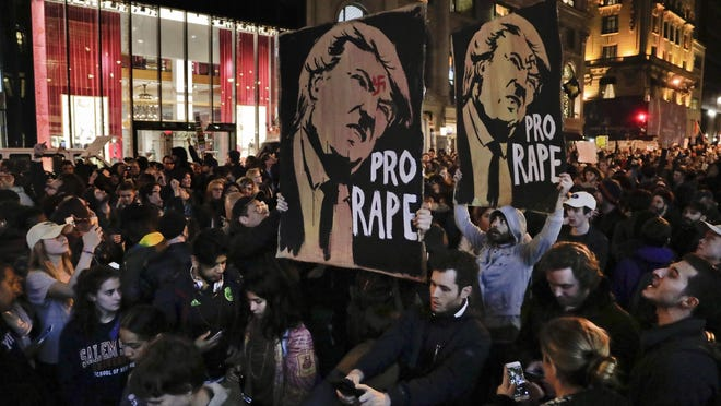 Protesters march along Fifth Avenue outside Trump Tower in Manhattan on Wednesday in opposition of Donald Trump's presidential election victory.
