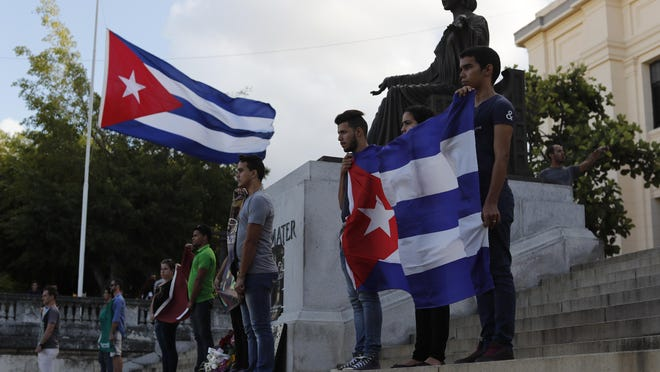 The Cuban flag is at half mast as students hold photos and flags at the university where Castro studied law as a young man, during a vigil in Havana, Cuba, Nov. 27, 2016. Castro, who led a rebel army to improbable victory in Cuba, embraced Soviet-style communism and defied the power of U.S. presidents during his half century rule, died at age 90.