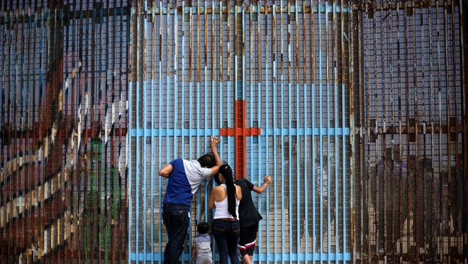 A family talks with with relatives through the US-Mexico border fence in Playas de Tijuana, in Tijuana, northwestern Mexico, on July 2. Mexican families reunite with their relatives living in the United States at the border between Tijuana, Mexico, and southern California.
