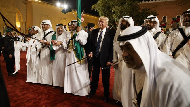 President Donald Trump holds a sword and sways with traditional dancers during a welcome ceremony at Murabba Palace, Saturday, May 20, 2017, in Riyadh.