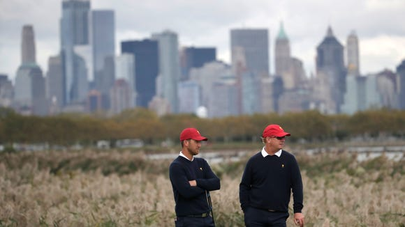 With the New York City skyline in the background, United States' teammates Kevin Chappell and Charley Hoffman, right, stand near the 10th green during the four-ball golf matches on the third day of the Presidents Cup at Liberty National Golf Club in Jersey City, N.J., Saturday, Sept. 30, 2017. (AP Photo/Julio Cortez)