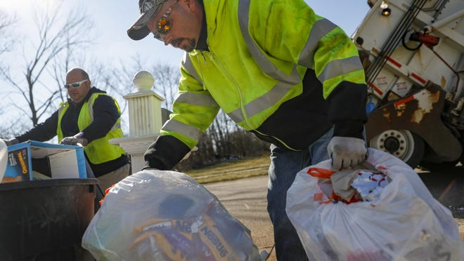 In this March 23, 2018, photo, Route driver Jaime Fisherback, right, and foreman Kenny Lane, left, collect refuse to load into a garbage truck as they work a residential route in Miamisburg, Ohio. Fifty years after two sanitation workers' deaths provoked an historic strike in Memphis, trash collection remains one of the nation's most dangerous jobs. In the first 10 days of 2018 alone, seven sanitation workers were killed in six states, the Solid Waste Association of North America says. The association is working to pass legislation in 16 states, including Ohio, New York, Illinois and Kentucky, creating penalties for motorists who don't slow down and give garbage collectors enough space. (AP Photo/John Minchillo)
