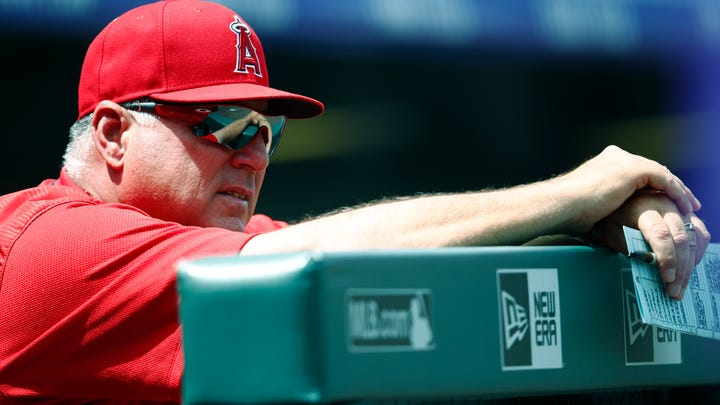 Los Angeles Angels manager Mike Scioscia leans over the dugout rail as he looks on against the Colorado Rockies in the first inning of an interleague baseball game Wednesday, May 9, 2018, in Denver. (AP Photo/David Zalubowski)