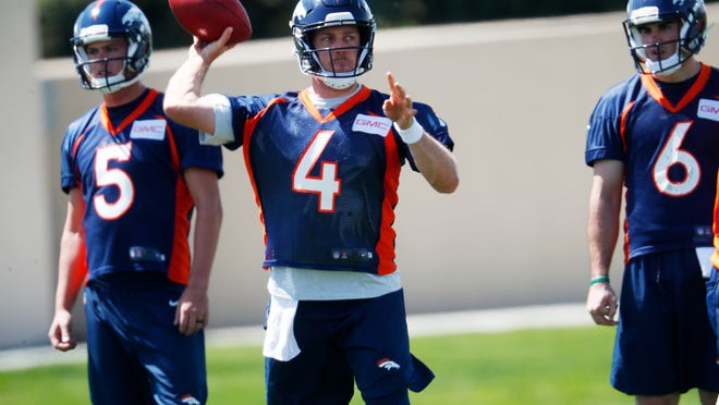 Denver Broncos quarterback Case Keenum, (4) takes part in a drill as quarterbacks Nick Stevens, (5) and Chad Kelly (6) look on during an NFL football minicamp session Tuesday, May 22, 2018, at the team's headquarters in Englewood, Colo.(AP Photo/David Zalubowski)