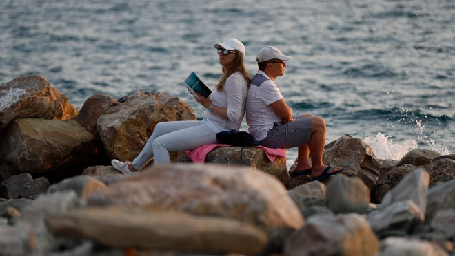 FILE - In this Friday, June 22, 2018 filer, Russian tourists enjoy the Black Sea waterfront during the 2018 soccer World Cup in Sochi, Russia. Sochi in the summer is a whole lot different than what fans saw during the Winter Olympics. The snow is replaced by lots of sun as Russia's summertime playground explodes in a scene more akin to Southern California or Miami Beach than Siberia. World Cup fans have been taking advantage of the beaches, waterparks and other warm-weather activities, and teams have been eager to train there. (AP Photo/Rebecca Blackwell, File)
