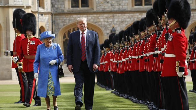 In this July 13, 2018, photo, U.S. President Donald Trump with Queen Elizabeth II, inspects the Guard of Honour at Windsor Castle in Windsor, England. (AP Photo/Pablo Martinez Monsivais)