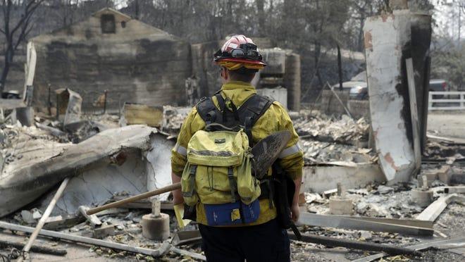 Capt. Scott Fisher, with the San Bernardino County Fire Department, surveys a wildfire-damaged neighborhood, Sunday, July 29, 2018, in Keswick, Calif.