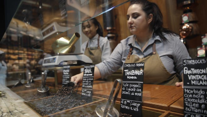 In this photo taken on Tuesday, Sept. 4, 2108, employees work at the Starbucks store in Milan, Italy. Starbucks opens its first store in Italy Friday, betting that premium brews and novelties like a heated marble-topped coffee bar will win patrons in a country fond of its espresso rituals. Decades ago, Milan's coffee bars had inspired the chain's vision. Starbucks hopes clients will linger at Starbucks Reserve Roastery, where they can watch beans being roasted, sip Reserve coffee or have cocktails at a mezzanine-level bar in a cavernous space that once was a post office near the city's Duomo, or cathedral. (AP Photo/Luca Bruno)