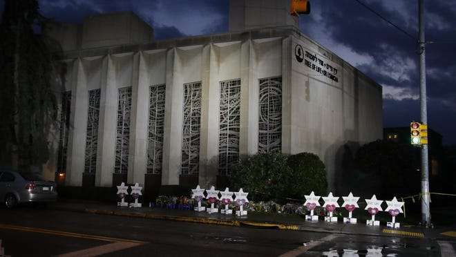 A memorial of flowers and stars line the sidewalk outside the Tree of Life Synagogue Sunday, Oct. 28, 2018, in remembrance of 11 people killed when a shooter opened fire during services Saturday, Oct. 28, 2018 in Pittsburgh.
