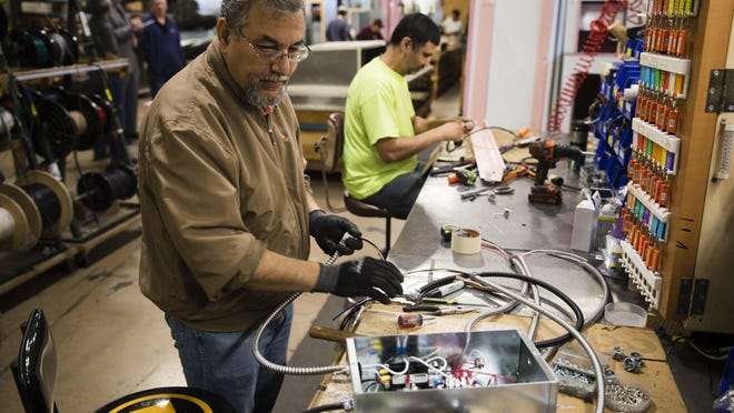 In this Thursday, Oct. 18, 2018, photo Sarmad Eskandar, left, and Mustpha Damen work on electrical components at the Howard McCray's commercial refrigeration manufacturing facility in Philadelphia.