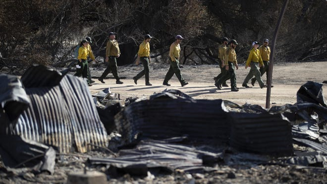Firefighters walk arrive at decimated Paramount Ranch for a meeting with U.S. Secretary of the Interior Ryan Zinke Thursday, Nov. 15, 2018, in Agoura Hills, Calif. The landmark film location burned to the ground by the Woolsey Fire.