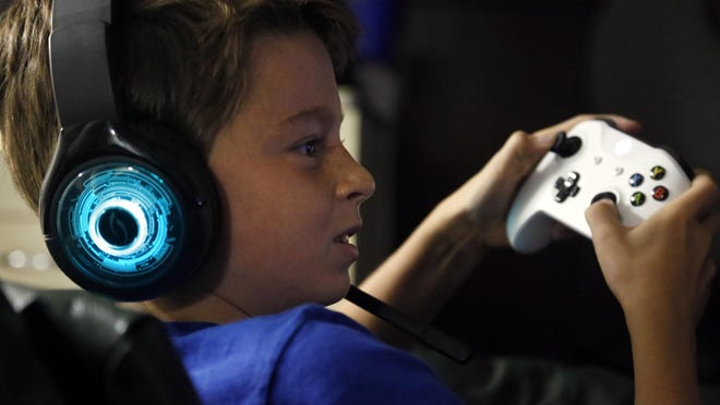 In this Oct. 6, 2018, photo, Henry Hailey, 10, plays the online game Fortnite in the early morning hours in the basement of his Chicago home. His parents are on a quest to limit screen time for him and his brother.