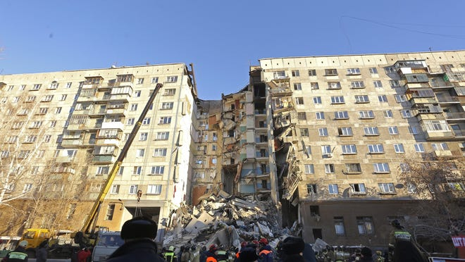 Emergency Situations employees working at the scene of a collapsed apartment building in Magnitogorsk, a city of 400,000 people, about 870 miles southeast of Moscow, Russia, Dec. 31, 2018. Russian emergency officials say that at least four people have died after sections of the apartment building collapsed after an apparent gas explosion in the Ural Mountains region.