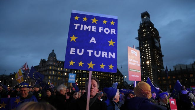 Pro-European demonstrators hold posters at Parliament Square in London, Jan. 15, 2019.