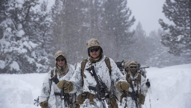 U.S. Marines walk along a snow-covered trail during their advanced cold-weather training at the Marine Corps Mountain Warfare Training Center on Feb. 10, 2019, in Bridgeport, Calif.