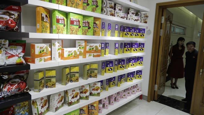 In this March 13, 2019, photo, employees peek through a door into a showroom at a food factory in Pyongyang, North Korea. North Korean factories are filling city store shelves with ever better and fancier snack foods and sugary drinks, while government officials and international aid organizations warn the nation could be on the verge of a major food crisis.