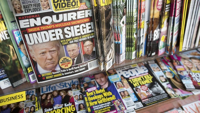 In this July 12, 2017 file photo, an issue of the National Enquirer featuring President Donald Trump on its cover is displayed on a newsstand in a store in New York. The tabloid's owner, American Media announced Thursday, April 18, 2019, that it is selling the supermarket weekly to James Cohen, the former head of the airport newsstand company Hudson News.