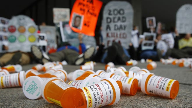 Containers depicting OxyContin prescription pill bottles rest on the ground as protesters demonstrate against the FDA's opioid prescription drug approval practices, Friday, April 5, 2019, in front of the Department of Health and Human Services' headquarters in Washington.