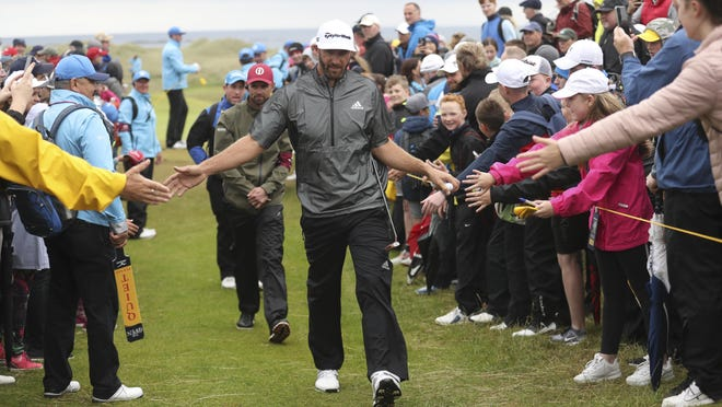 Dustin Johnson touches hands with spectators as he walks to the 17th tee during a practice round on Wednesday.