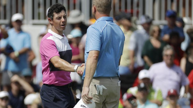 Rory McIlroy, left, shakes hands with playing partner Nate Lashley as they leave the 18th green Saturday during the third round of the World Golf Championships-FedEx St. Jude Invitational.
