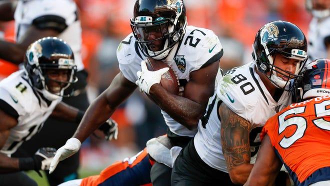 Jacksonville Jaguars running back Leonard Fournette, center, runs with the ball during the second half of an NFL football game against the Denver Broncos, Sunday, Sept. 29, 2019, in Denver. (AP Photo/David Zalubowski)