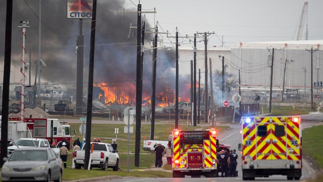Corpus Christi police and fire departments respond to a large fire at Interstate Highway 37 and Buddy Lawrence Drive, near the city's Citgo refinery, on Monday.