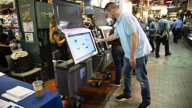 "FILE - In this June 13, 2019, file photo, Steve Marcinkus, an Investigator with the Office of the City Commissioners, demonstrates the ExpressVote XL voting machine at the Reading Terminal Market in Philadelphia. Nearly 1 in 5 U.S. voters will cast ballots this year on devices that look and feel like the discredited paperless voting machines they once used, yet leave a paper record of the vote. Computer security experts are warning that these so-called ballot-marking devices pose too much of a risk. Ballot-marking machines were initially developed not as primary vote-casting tools but as ""accessible"" alternatives for the disabled. They print out paper records that are scanned by optical readers that tabulate the vote. They cost at least twice as much as hand-marked paper ballots, which computer scientists prefer because paper can't be hacked. (AP Photo/Matt Rourke, File)"