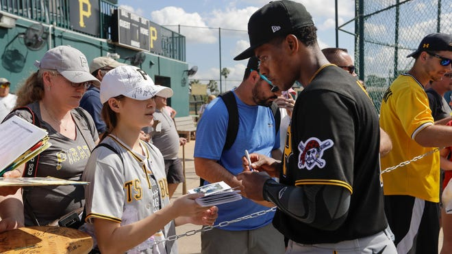 Pittsburgh Pirates' Ke'Bryan Hayes, right, gives autographs after a spring training baseball workout Monday, Feb. 17, 2020, in Bradenton, Fla. (AP Photo/Frank Franklin II)