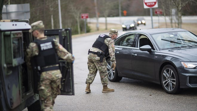 A member of the Rhode Island National Guard Military Police directs a motorist with New York license plates at a checkpoint on I-95 over the border with Connecticut where New Yorkers must pull over and provide contact information and are told to self-quarantine for two weeks, Saturday, March 28, 2020, in Hope Valley, R.I. Rhode Island Gov. Gina Raimondo on Saturday ordered anyone visiting the state to self-quarantine for 14 days and restricted residents to stay at home and nonessential retail businesses to close Monday until April 13 to help stop the spread of the coronavirus. (AP Photo/David Goldman)