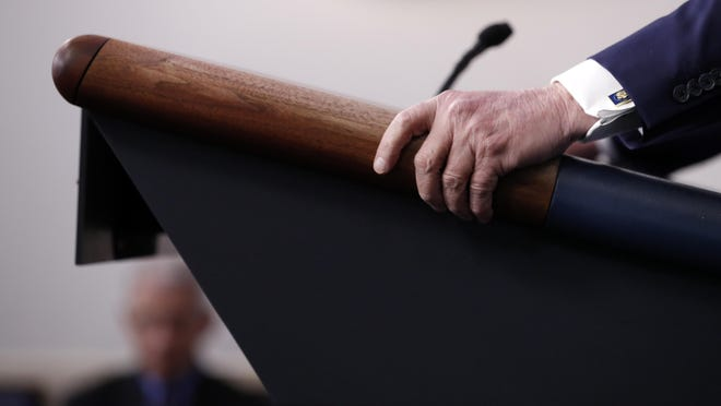 FILE - In this April 9, 2020, file photo President Donald Trump holds the podium as he speaks about the coronavirus in the James Brady Press Briefing Room of the White House in Washington. (AP Photo/Andrew Harnik, File)